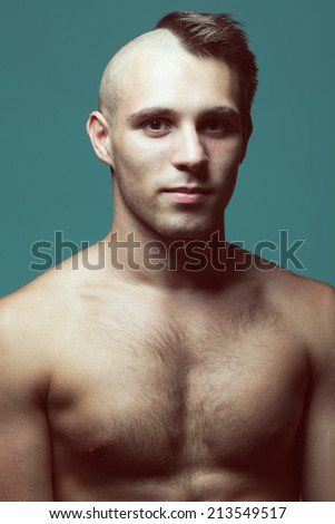 Male beauty concept. Handsome muscular male model posing over blue background. Half-shaved and healthy clean skin. Close up. Studio portrait - stock photo