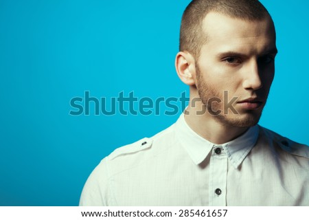 Male beauty concept. Portrait of fashionable young man with haircut wearing trendy shirt & posing over blue background. Casual street style. Copy-space. Close up. Studio shot - stock photo