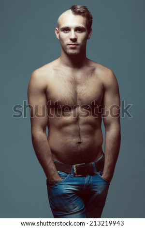 Male beauty concept. Portrait of handsome muscular male model in jeans with hands in pockets over gray background. Half-shaved or half-bald head and healthy clean skin. Fashion studio shot - stock photo