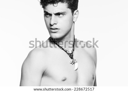Male beauty concept. Portrait of handsome muscular male model with ethnic necklaces posing over white background. Perfect glossy wet curly hair and healthy clean skin. Close up. Studio shot - stock photo