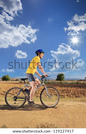 Male bicyclist riding a bike outdoors - stock photo