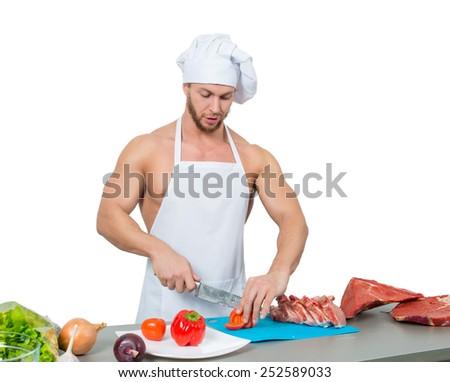 male bodybuilder chef cuts a tomato.  - stock photo
