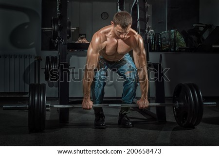 Male bodybuilder raises the bar in the gym. - stock photo