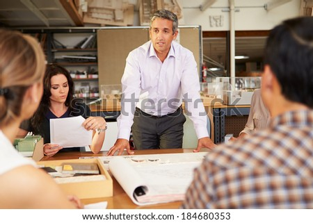 Male Boss Leading Meeting Of Architects Sitting At Table - stock photo
