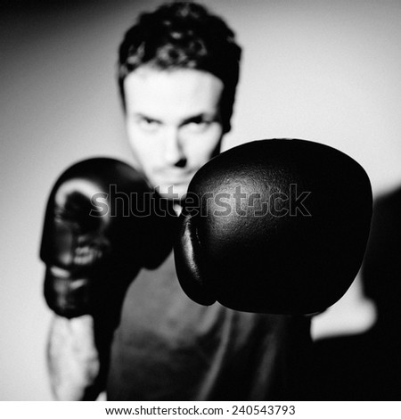 Male boxer looking at camera and punching. - stock photo
