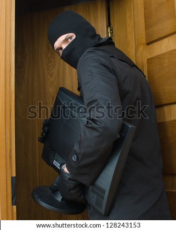Male burglar in mask breaking into the house and stealing monitor - stock photo