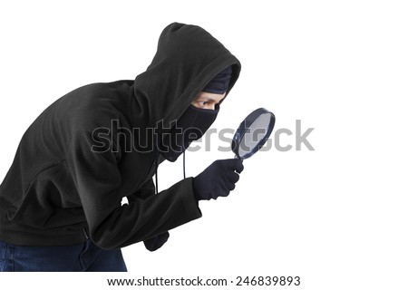Male burglar wearing a mask and uses magnifying glass for spying and find information - stock photo