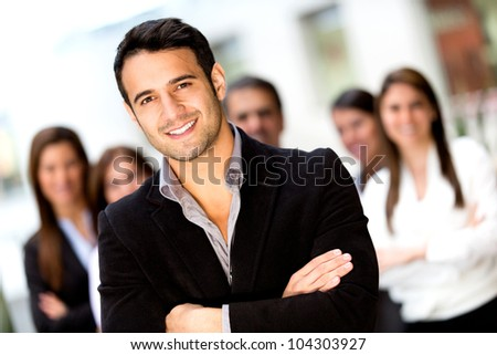 Male business leader looking confident with a group - stock photo
