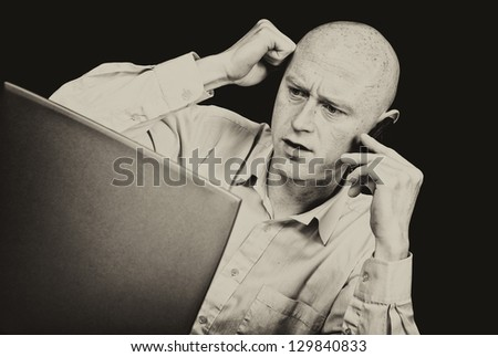 male businessman on phone looking into laptop frustrated - stock photo
