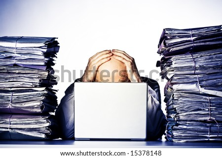 Male businessman sitting behind a laptop, his face hidden, with his hands on top of his head.  Two large piles of paperwork are piled on each side of the model, towering over his head. - stock photo