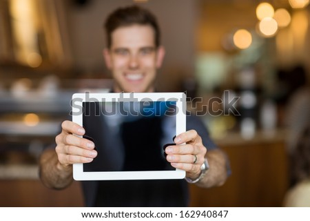 Male cafe owner showing digital tablet in cafeteria - stock photo