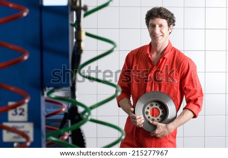 Male car mechanic, in red overalls, standing in commercial garage, holding vehicle part, smiling, portrait - stock photo