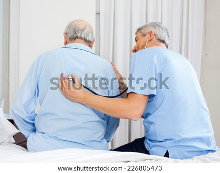 Male caretaker examining senior man's back with stethoscope in bedroom at nursing home - stock photo