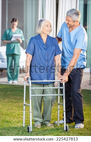 Male caretaker helping senior woman to use walking frame with female nurse in background at nursing home lawn - stock photo