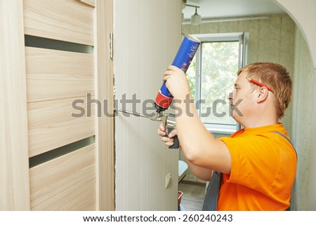 Male carpenter at interior wood door installation working with foam - stock photo
