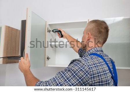 Male Carpenter Drilling In Cabinet With Electric Cordless Drill - stock photo