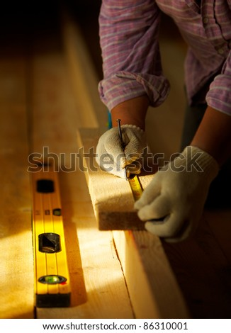 male carpenter is working with wooden plank - stock photo