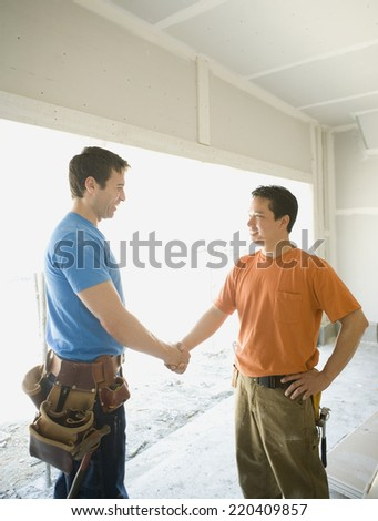 Male carpenters shaking hands inside construction site - stock photo