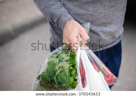 Male carrying bag in his hand after shopping. Closeup of bag full of fruits and vegetables.  - stock photo