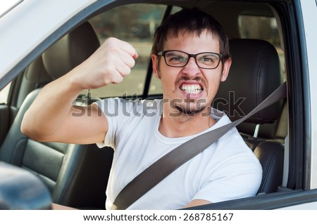 Male caucasian angry driver is showing his fist and mad face - stock photo
