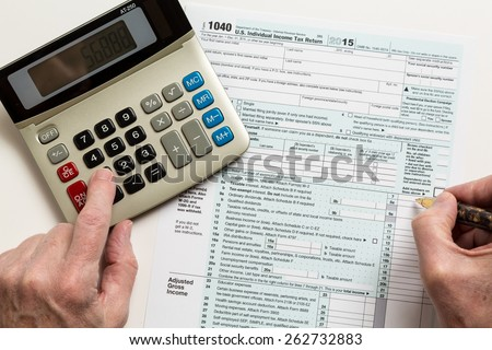 Male caucasian hand holding pen above USA tax form 1040 for year 2015 and calculator illustrating completion of tax forms for the IRS - stock photo