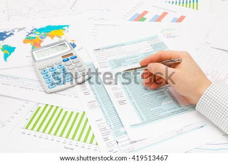Male checking 1040 USA Tax Form with silver ball pen - stock photo