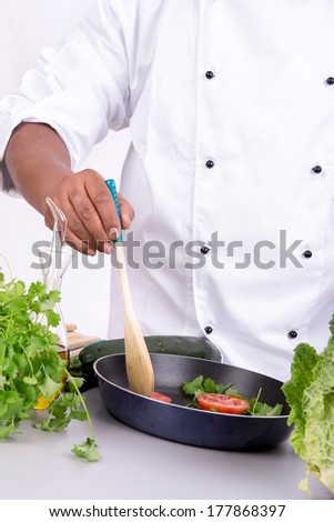 Male chef arms with fruits and vegetables cooking - stock photo