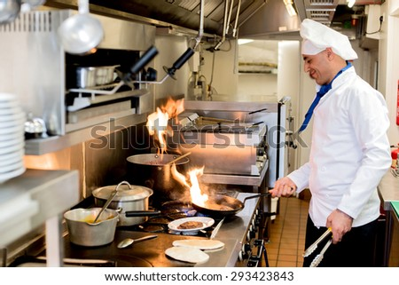 Male chef cooking with flame in a frying pan on kitchen - stock photo