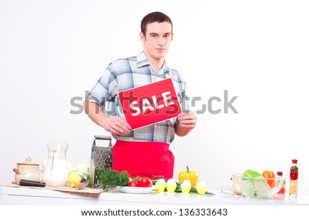male chef in the kitchen holding a red plate with the inscription sale - stock photo