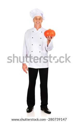 Male chef in uniform holding a pumpkin - stock photo