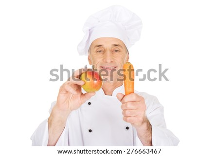 Male chef in uniform holding apple and carrot - stock photo