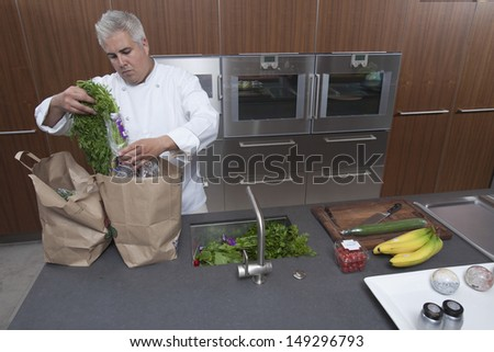 Male chef unpacking groceries from paper bags in commercial kitchen - stock photo