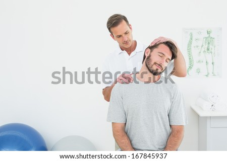 Male chiropractor doing neck adjustment in the medical office - stock photo