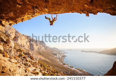Male climber has just fell of a cliff while rock climbing. Beautiful view of coast in the background. - stock photo