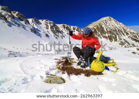Male climber resting while preparing crampons on snow covered valley - stock photo