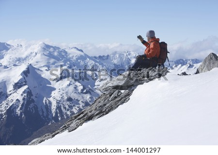 Male climber taking picture of snowy mountains on peak - stock photo