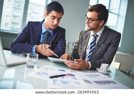 Male colleagues discussing new project or data in office - stock photo