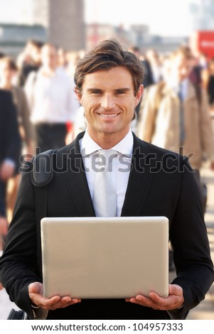 Male commuter in crowd using laptop - stock photo