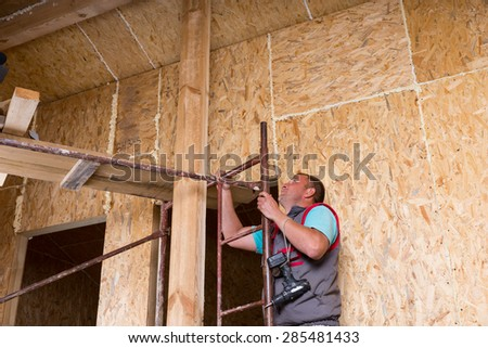 Male Construction Worker Builder Holding Cordless Drill Climbing Up Ladder of Scaffolding Inside Unfinished Home with Exposed Particle Plywood Boards Frame - stock photo