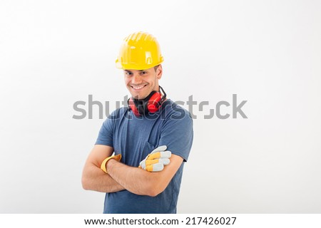 Male construction worker wearing a yellow  hard hat and full protective gear smiling at the camera with his arms crossed. Isolated over white in horizontal format. - stock photo