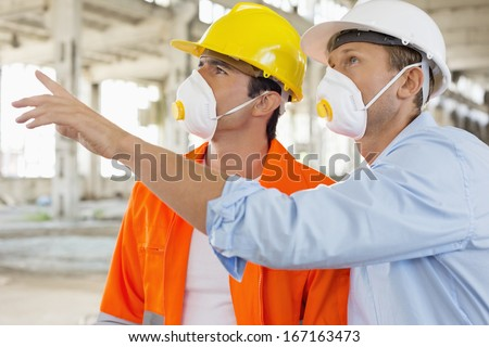 Male construction workers having a discussion at site - stock photo