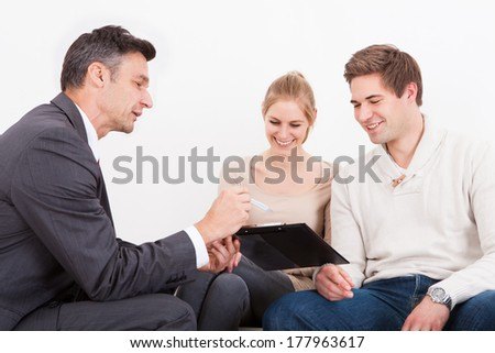 Male Consultant Showing Clipboard To Happy Young Couple - stock photo