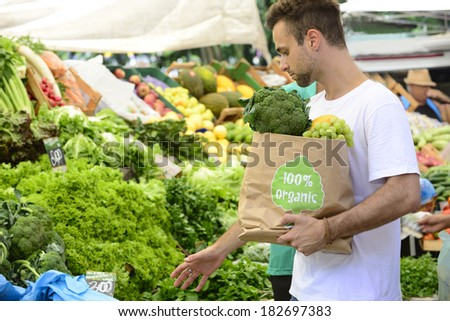 Male consumer at an open street market carrying a shopping paper bag with a 100% organic certified label full of fruit and vegetables. - stock photo