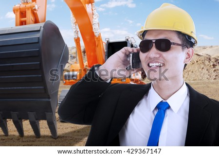 Male contractor talking on the mobile phone with an excavator on the background, shot outdoors - stock photo