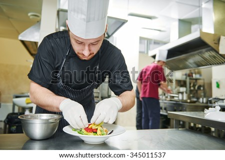 male cook chef decorating garnishing prepared salad dish on the plate in restaurant commercial kitchen - stock photo