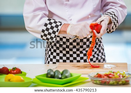 Male cook preparing food in the kitchen - stock photo