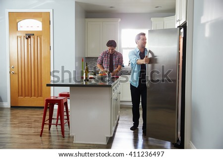 Male couple in the kitchen preparing a meal, opening fridge - stock photo