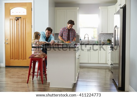 Male couple preparing a meal talk to their daughter in kitchen - stock photo