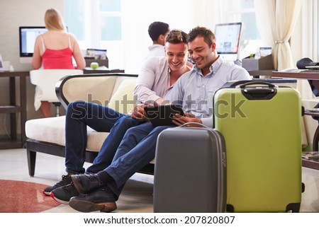 Male Couple Sitting In Hotel Lobby Looking At Digital Tablet - stock photo