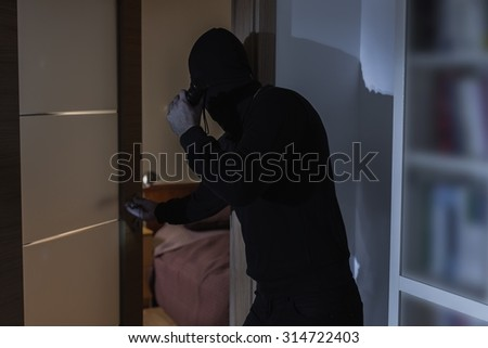 Male criminal in balaclava and black clothes - stock photo